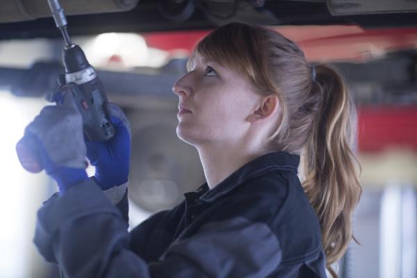 female car mechanic fixing car standing