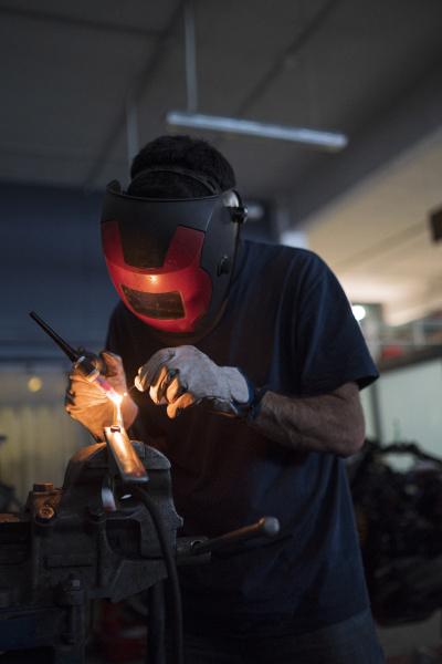 mechanic in a repair garage welding