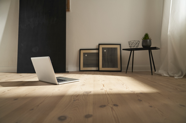 laptop on wooden floor in a