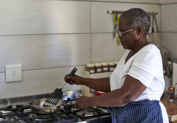senior woman cooking at gas stove