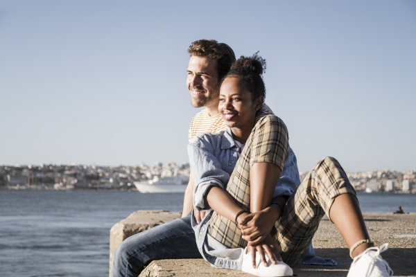 happy young couple sitting on pier