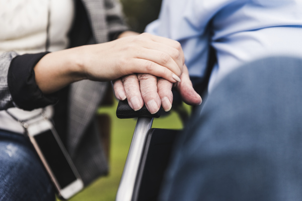young woman touching senior mans hand