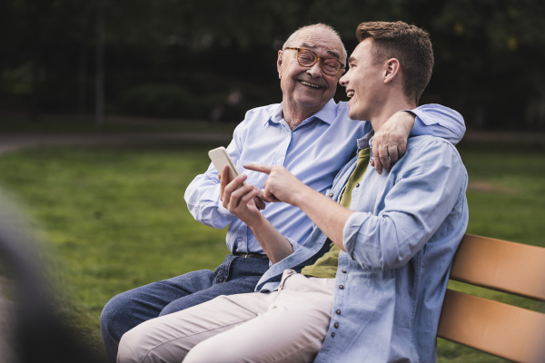senior man and grandson with smartphone