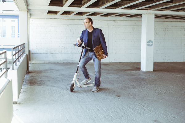 mature businessman with e scooter and