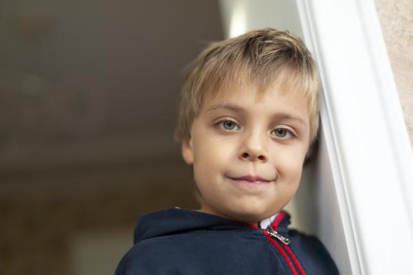 portrait of little boy leaning against