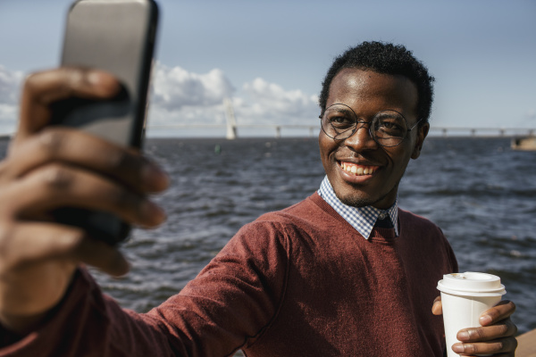 young man taking smartphone selfie at