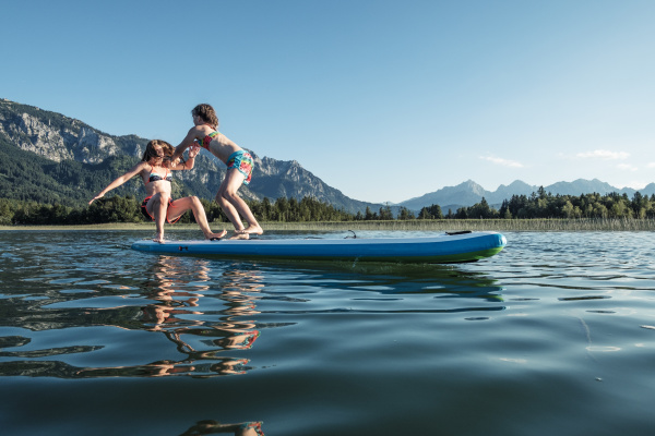 sisters fighting on paddle board lake