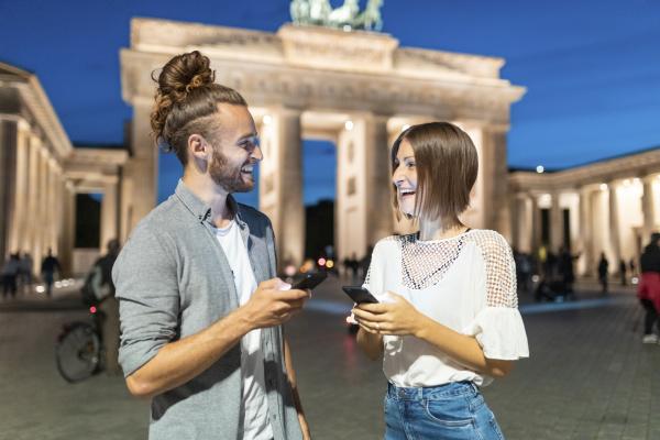 happy couple using smartphones at brandenburg