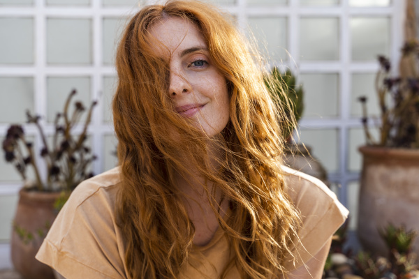 portrait of smiling redheaded young woman