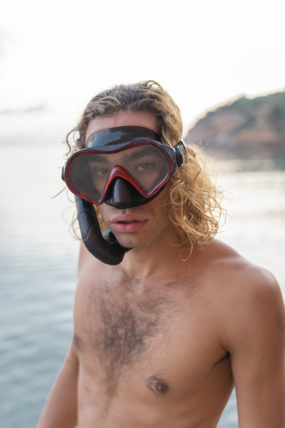 young man with snorkel on beach