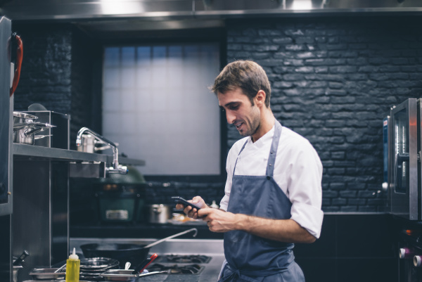chef using smartphone in the kitchen