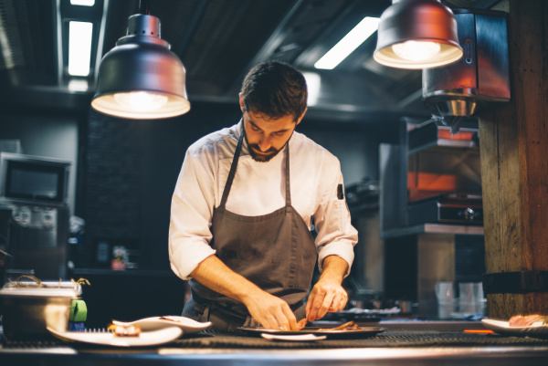 chef serving food on plates in