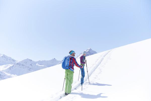 couple ski touring in the mountains