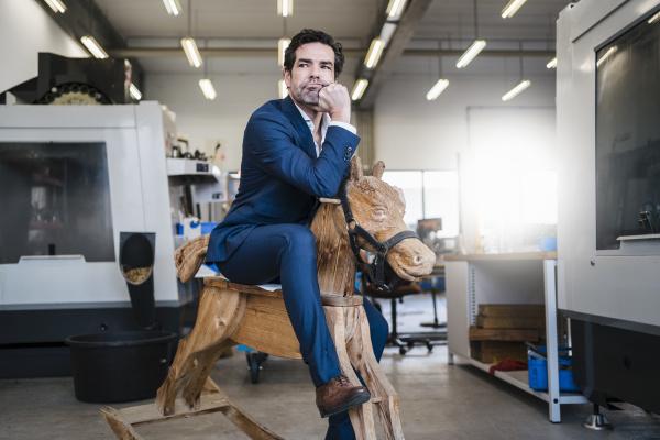 pensive businessman on wooden rocking horse