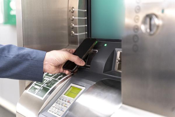 man holding smartphone on ticket machine