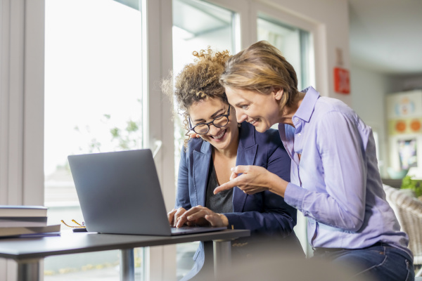 two happy businesswomen with laptop on