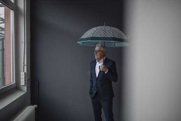 senior businessman holding umbrella