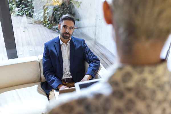 businessman looking at colleague in lounge