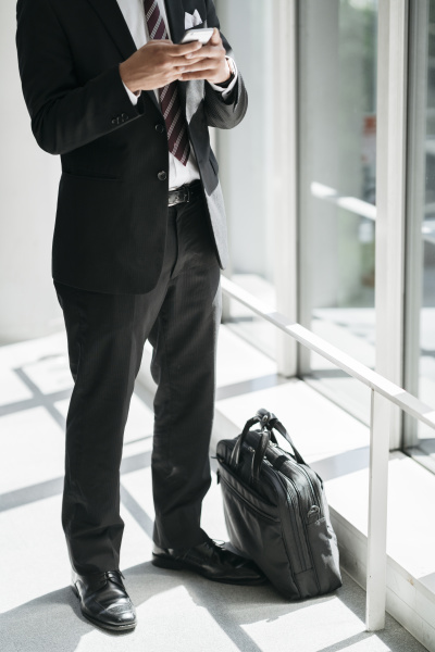 low section of businessman using cell