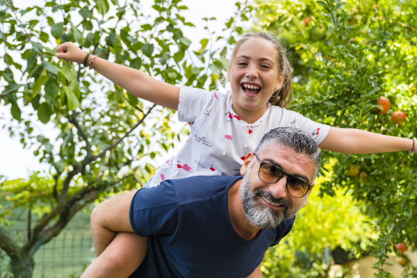 father carrying happy daughter piggyback in