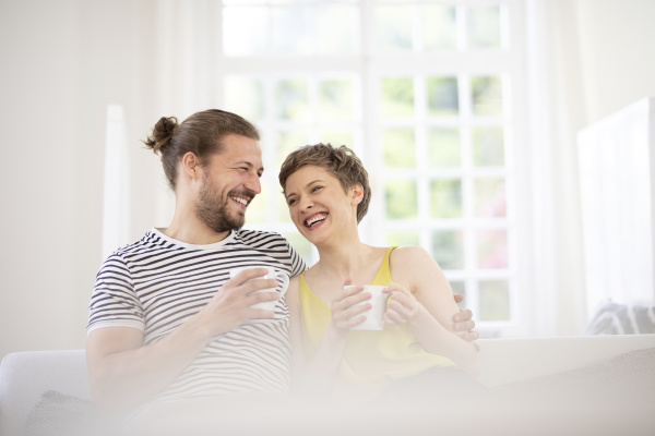 happy young couple holding cups on