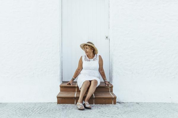 senior tourist sitting on stoop in