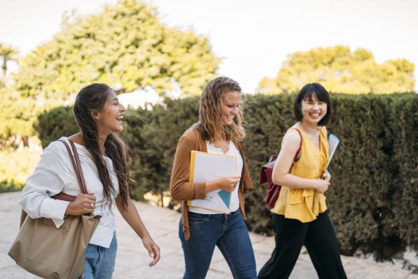 three happy female friends walking around