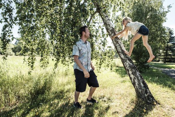 father watching daughter climbing a birch
