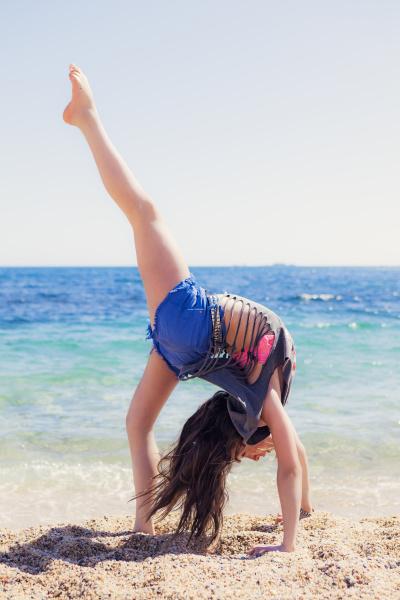 girl doing gymnastics on the beach