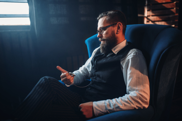 man sitting in armchair looking at