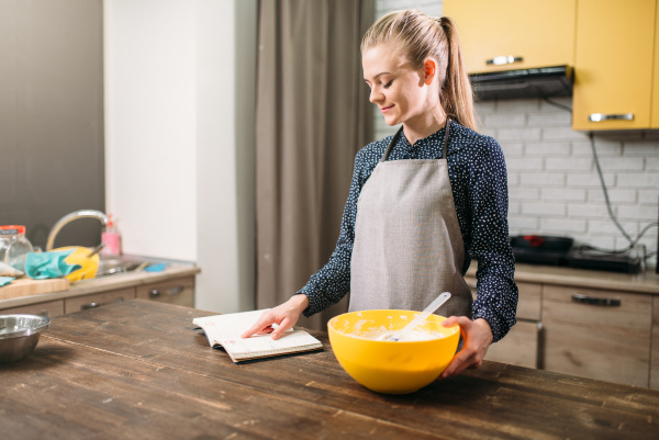 young woman in apron reading recipe