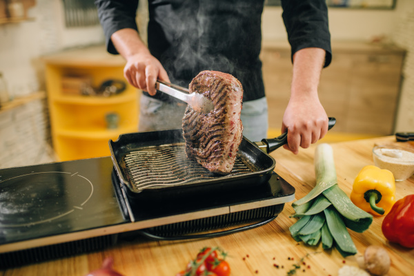 male person cooking meat in a