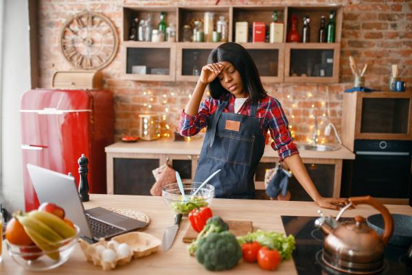 sleepy black woman in apron cooking