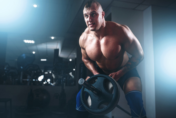 muscular athlete training with weight in