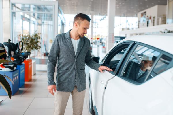 man buying new car in showroom