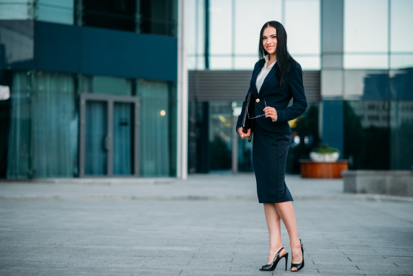 businesswoman poses against business center