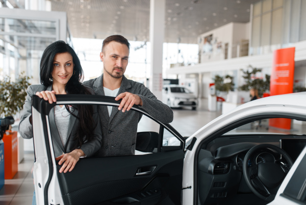 couple buying new car in showroom