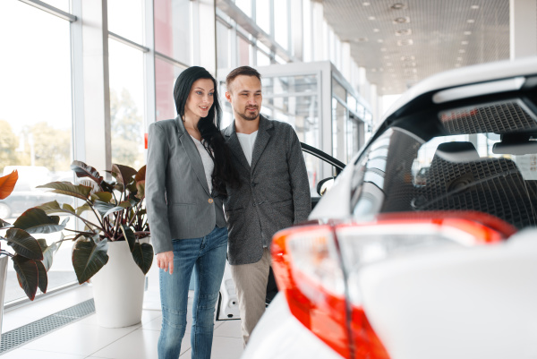 happy couple buying new car in