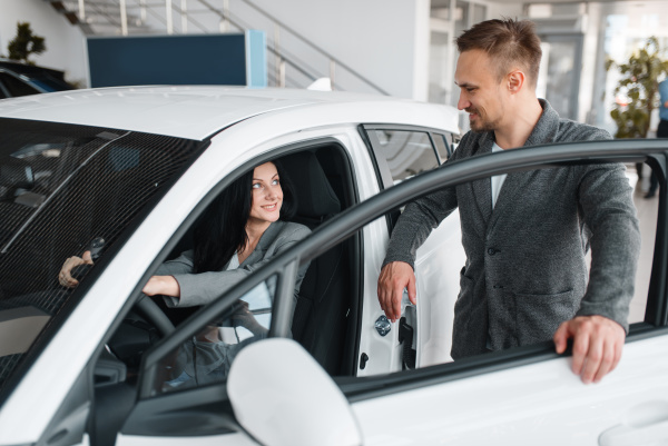 couple buying new car woman