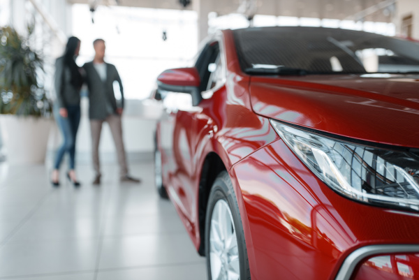 couple buying new red car in