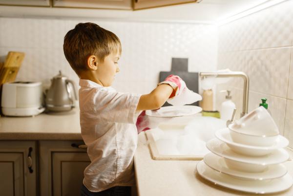 little boy in gloves washing dishes