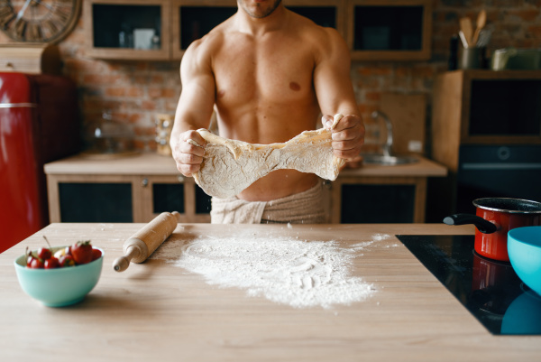 athletic husband in underwear cooking on