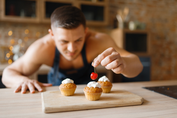 naked man in apron cooking dessert