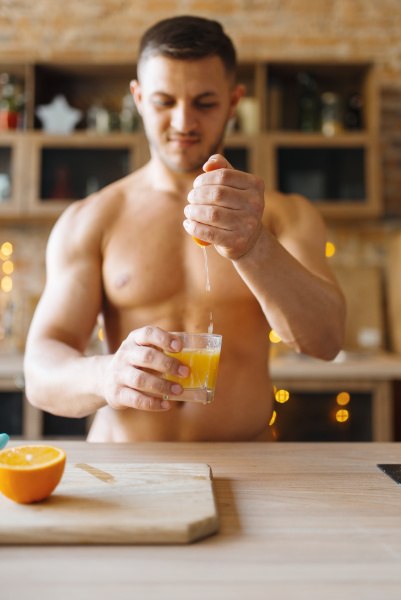 muscular man with naked body cooking