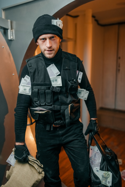robber in black uniform holds bags