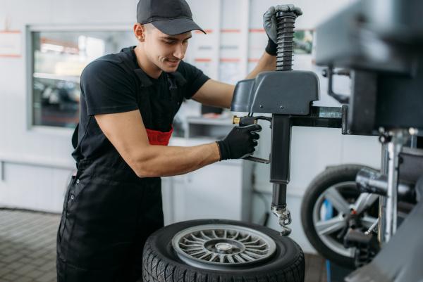mechanic fixing wheel on tire fitting