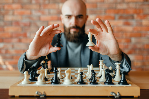 male chess player holds white and