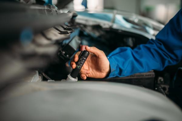 male, technician, checks, brake, fluid, level - 28076438