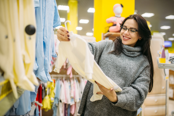 happy future mother choosing clothes in