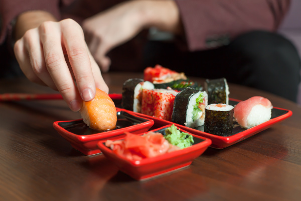 man, eats, sushi, roll, with, hands - 28077408